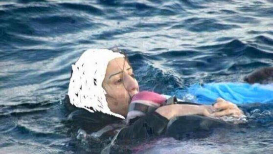 This photo shows a Syrian mother trying to hold her baby above the water