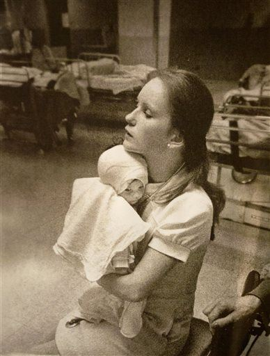 In this photo taken in 1977 and provided by Albany Medical Center, nurse Susan Berger cuddles infant Amanda Scarpinati, who had been severely burned by a steam vaporizer at home, in the pediatric unit at Albany Medical Center in Albany N.Y. Scarpinati kept the hospital's annual report that published the photo and was comforted by the picture when she was bullied for her burn scars as a child. She recently used social media to learn Berger's identity so she could thank her for her loving care. The two women were reunited at the hospital on Tuesday. (Carl Howard/Albany Medical Center via AP)