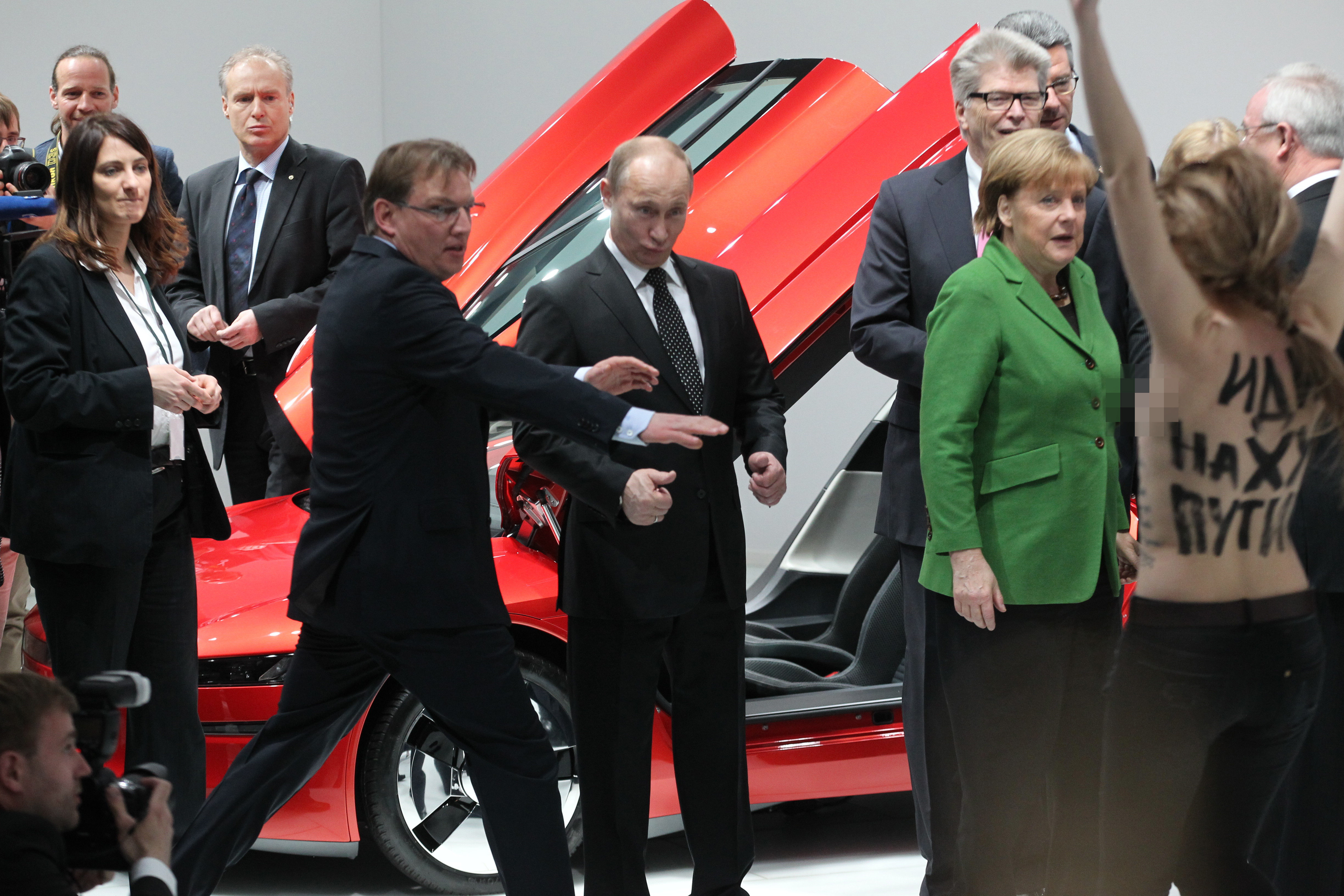 "HANOVER, GERMANY - APRIL 08: Russian President Vladimir Putin (C) is attacked by an activist (R) of the Ukrainian women rights group 'Femen' as German Chancellor Angela Merkel looks on during their visit of the industrial exhibition ""Hannover Messe"" on April 8, 2013 in Hannover, Germany. More than 100 Russian companies are exhibiting their industrial productions. (Photo by Sasha Mordovets/Getty Images)"