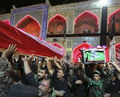 Mourners and militiamen chant slogans against the Islamic State group as they carry the flag-draped coffins of two members of the Peace Brigades, a Shiite militia group loyal to Shiite cleric Muqtada al-Sadr, during their funeral procession inside the shrine of Imam Ali in Najaf, 100 miles (160 kilometers) south of Baghdad, Iraq, Saturday, Nov. 7, 2015. The militiamen were killed in Ramadi during fighting with Islamic State militants, their families said. (AP Photo/Anmar Khalil)