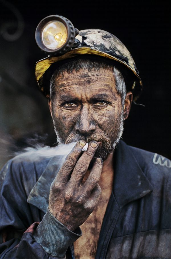"Description/Caption: Coal miner smoking a cigarette, Pol-e-Khomri, Afghanistan, 2002 ""A coal miner, dark with the dust from the mine, slowly registers his presence against the darker field of the mine's deep shaft in central Afghanistan. Light from his lamp and the trail of white smoke from his cigarette focus attention. Then the whites of his eyes emerge, then his fingertips. Gradually he appears. This difficult image mirrors the tough lives of miners in Afghanistan, men who live perilously under threatening conditions."" - Phaidon 55 ""The image of the coal miner besmeared with dust is an iconic one in the history of photography. The white eyes looking out of the blackened skin make for a stark, almost graphic, contrast. This miner works in the Pol-e-Khomri mine, which has one of the richest coal seams in the country, but the mine is also one of most dangerous, with many fatalities."" - Iconic Images Magnum Photos, NYC44609, MCS2002002 K006 Steve Mccurry_Book Looking East_Book Iconic_Book PORTRAITS_book PORTRAITS_APP final print_MACRO final print_Sao Paulo final print_Milan final print_Birmingham retouched_Sonny Fabbri 07/31/2013"